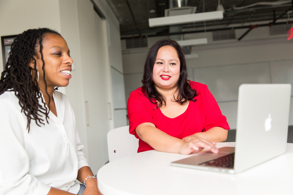 Confident women talking while working with laptop