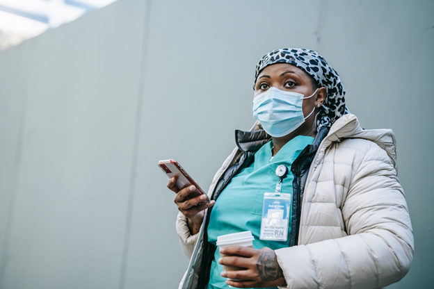 healthcare worker wearing a mask and using their phone