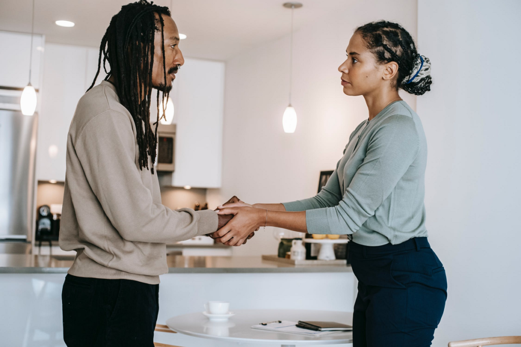 male client and female psychotherapist shaking hands and looking at each other