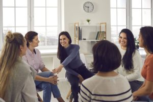 smiling female therapist supporting and motivating young women in group therapy session