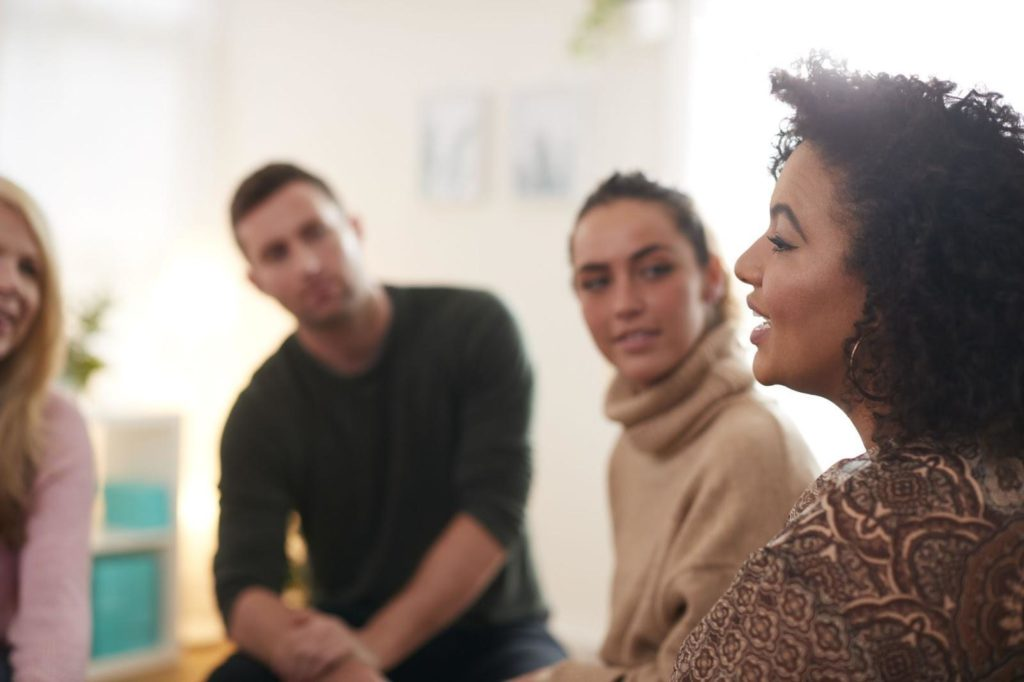 Woman Speaking At Support Group Meeting For Mental Health