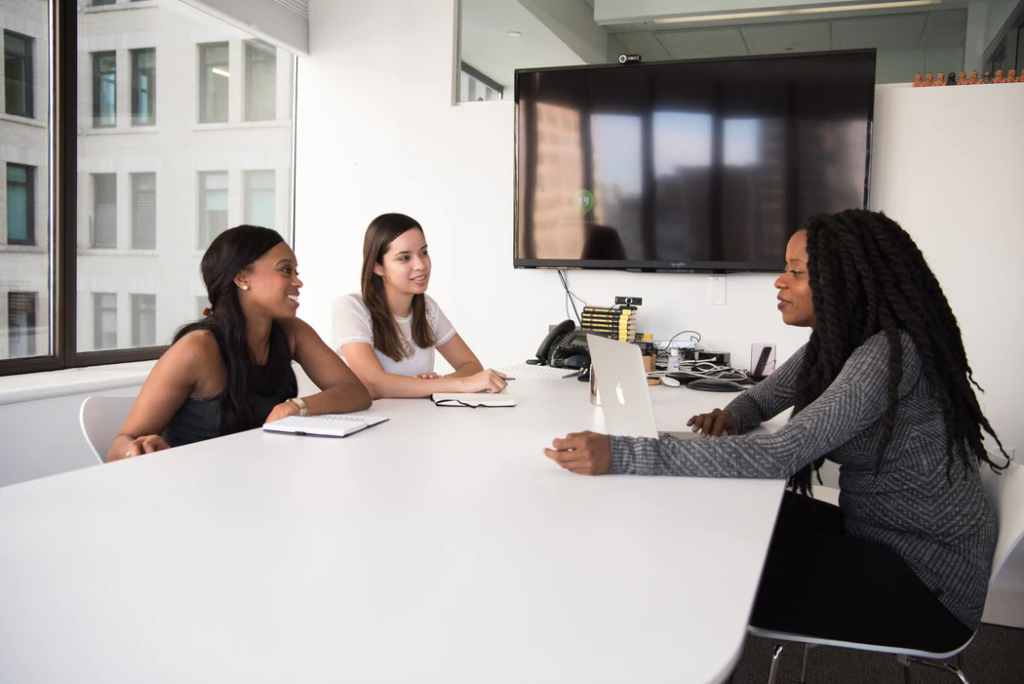 Three businesswomen using technology while sitting in immaculate office